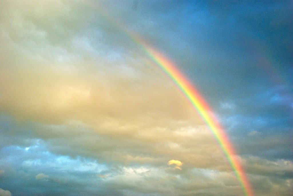 rainbow in sky with white and dark clouds