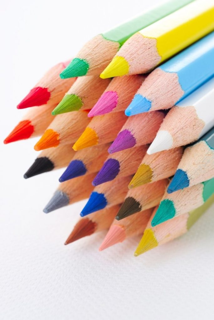 sharpened colored pencils in stack on white background