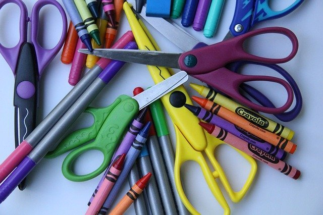crayons and scissors in pile on gray background