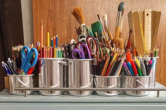 scissors colored pencils rules markers and paintbrushes in silver cans