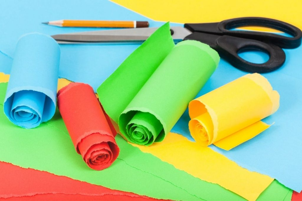 Different colored cardstock papers in rolls with pencil and scissors - paper crafts for kids