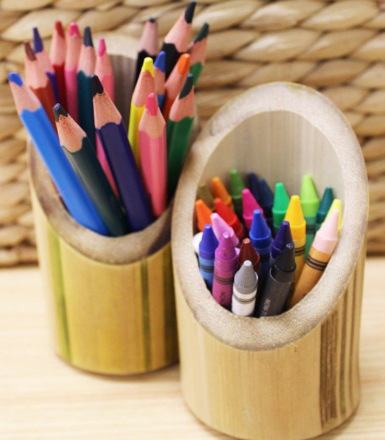colored pencils and crayons in bamboo cups in front of basket