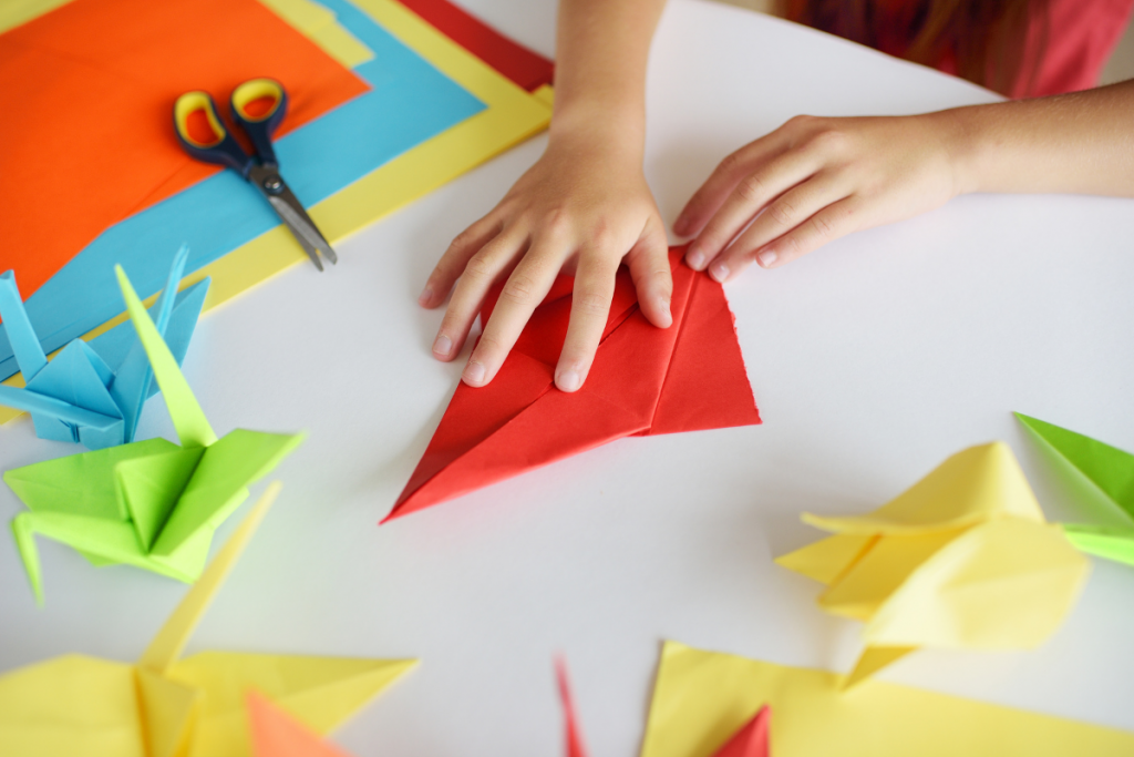 Child hands folding red paper into origami