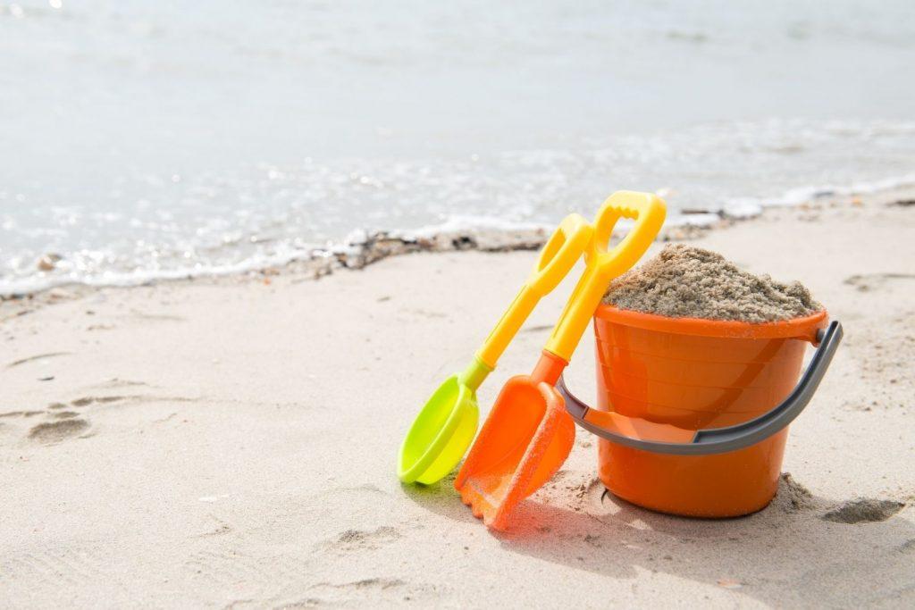 Orange pail filled with sand plus shovels on beach shore