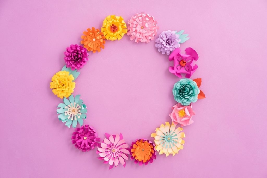 Wreath made of multicolored paper flowers on pink background