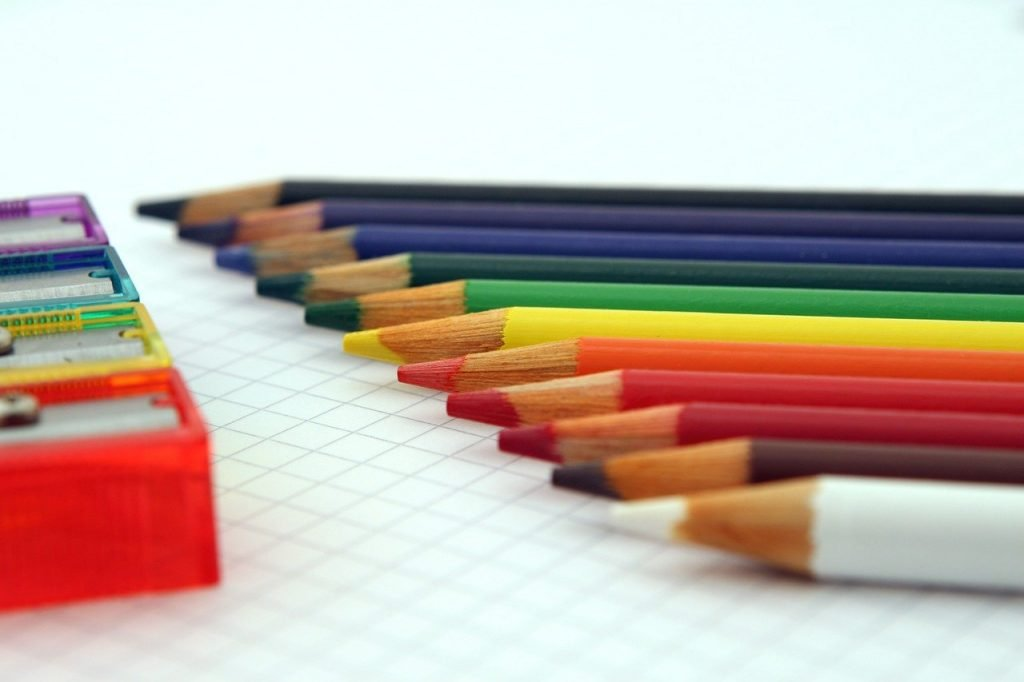 rainbow display of colored pencils with pencil sharpeners
