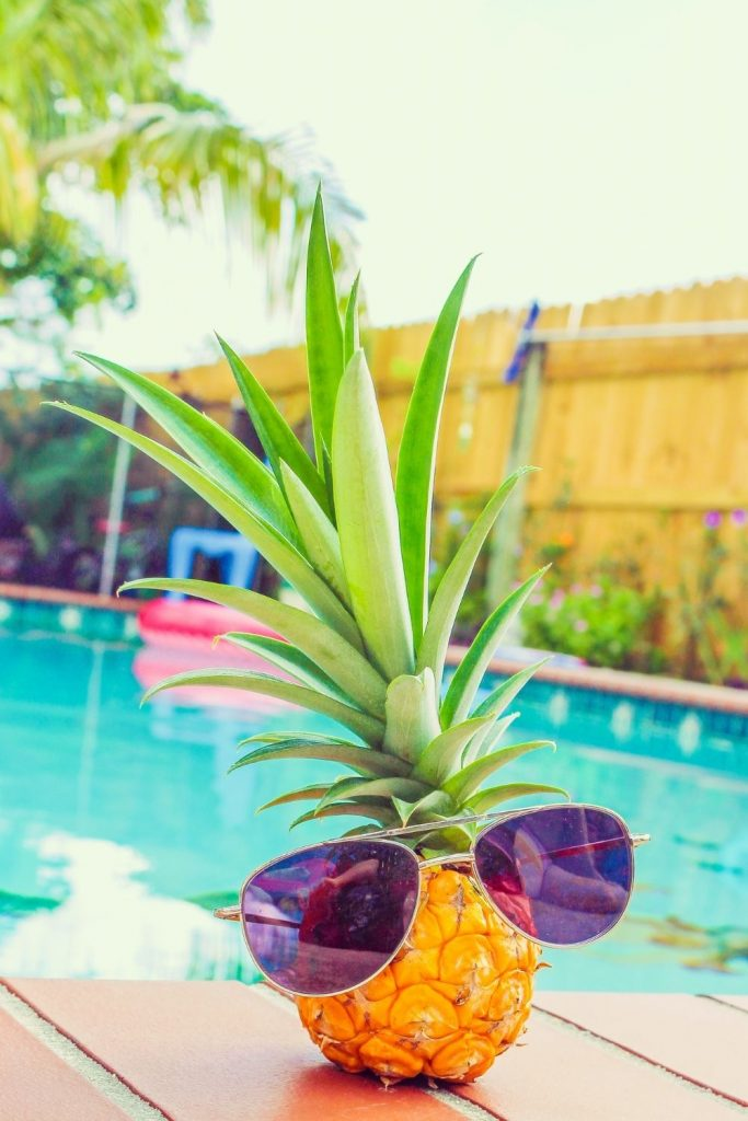 Pineapple with sun glasses in front of backyard pool