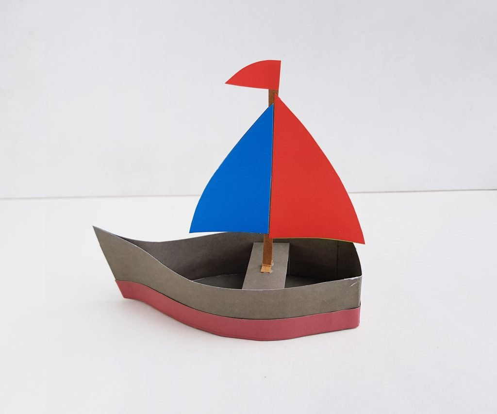 red blue and brown paper boat on white background - making a paper boat