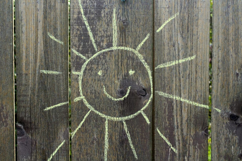 chalk drawn yellow sun on brown fence - summer themed pictionary game