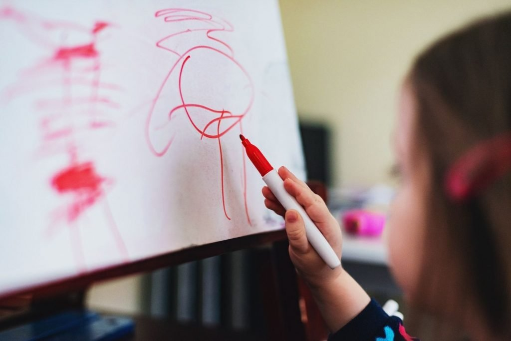 Girl drawing on pad of paper with red pen