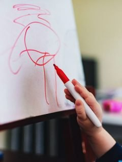 girl drawing on paper with red pen