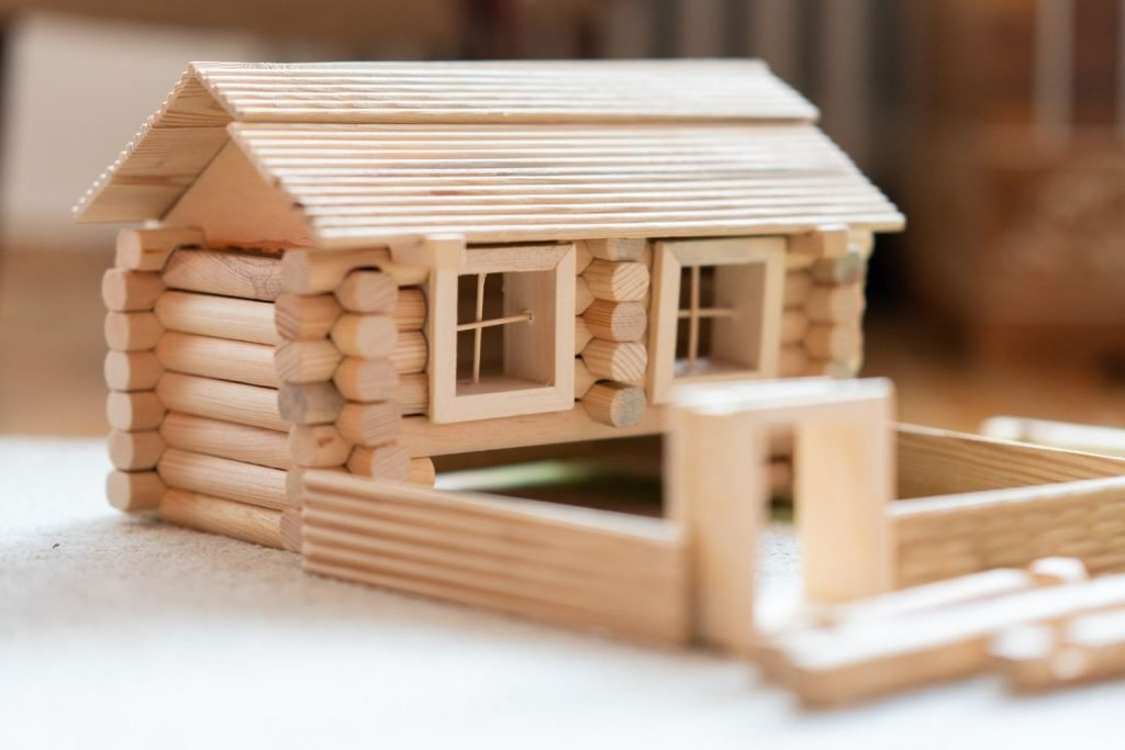 Wood building toy shaped into a log cabin