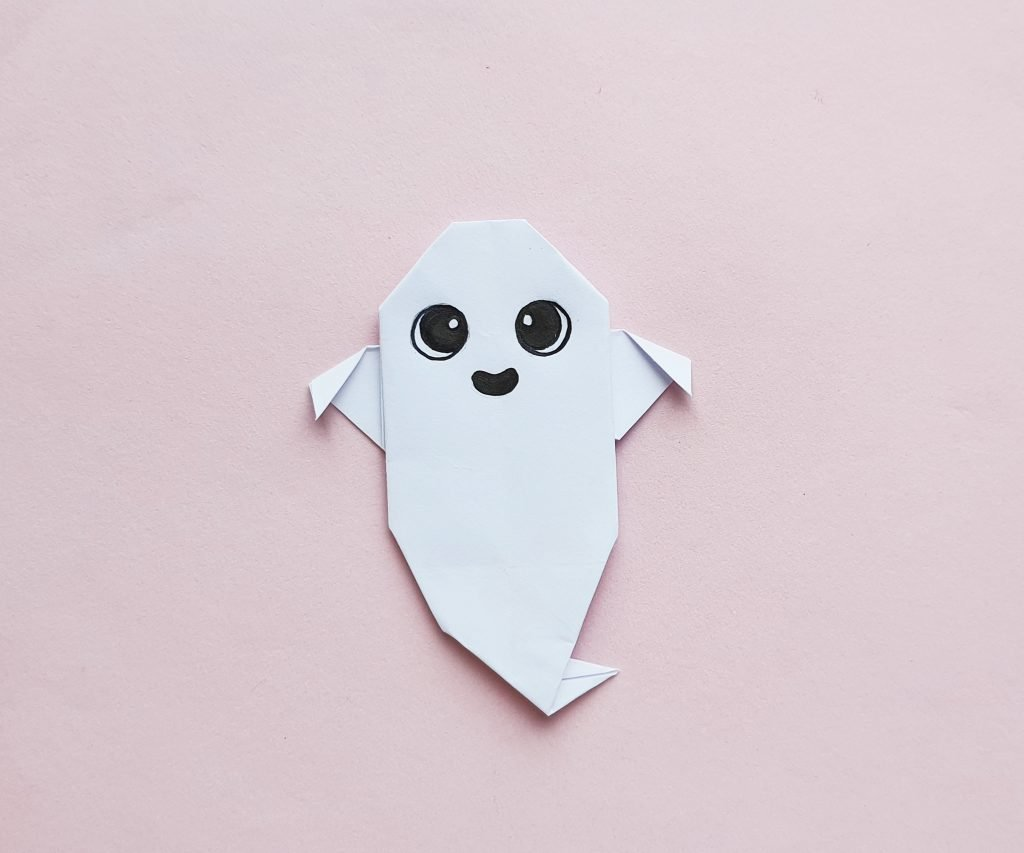 origami paper ghost on pink background